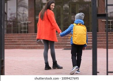 Cute little boy going to school with his mother