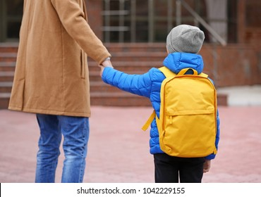 Cute little boy going to school with his father