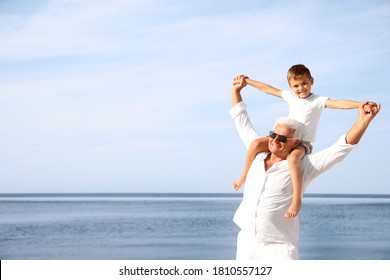 Cute little boy with grandfather spending time together near sea