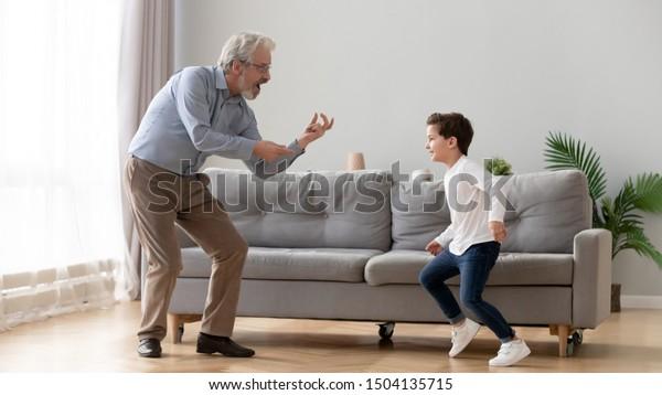 居間で年老いたおじいちゃんと踊りを楽しみ、幸せな2世代の現役家庭のおじいちゃんと小さな孫が家で一緒に楽しく遊んでいる
