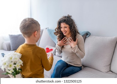 Cute little boy greeting his mother at home. Mother's day concept. Happy mother's day! Child son congratulates moms and gives her a postcard and flowers.