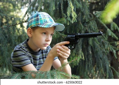 cute little boy with the gun playing in a park