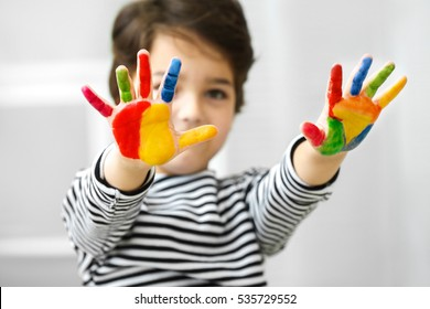 Cute little boy with hands in paint on blurred background