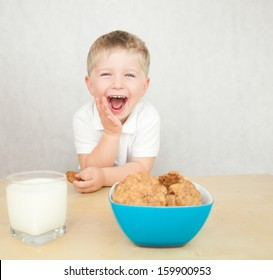 Cute little boy is having a breakfast. Child eating cookies and drinking milk.