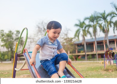 Cute little boy having fun on red kids riding from children slides in beautiful summer garden on warm and sunny day outdoors. Active summer playing for kids.