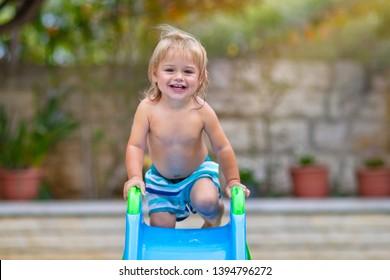 Cute little boy having fun in backyard, with pleasure riding a water slide on the beach resort, happy child enjoying summer holidays