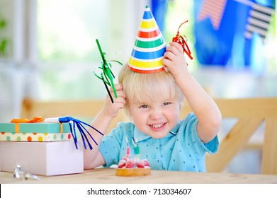 Cute little boy having fun and celebrate birthday party with colorful decoration and cake. Child with sweets, candy, whistle/blower/horn and festive gifts. Preschooler or toddler birthday party.