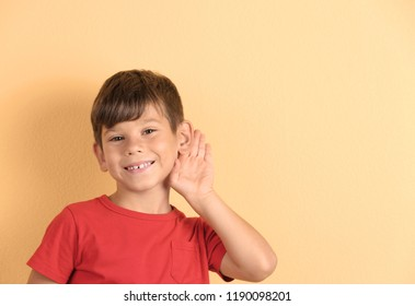 Cute little boy with hearing problem on color background. Space for text
