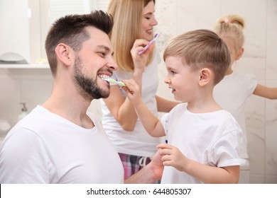 Cute little boy helping his father to brush teeth in bathroom
