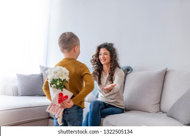 Cute little boy hiding present for her mother behind back, close up. Mother's day concept. Rear view of lad with bunch of beautiful flowers behind back preparing nice surprise for his mother