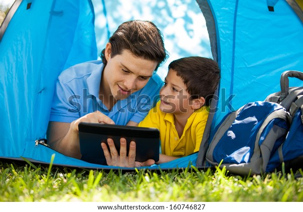 Cute little boy and his dad using a tablet computer and relaxing on a tent on a camping trip