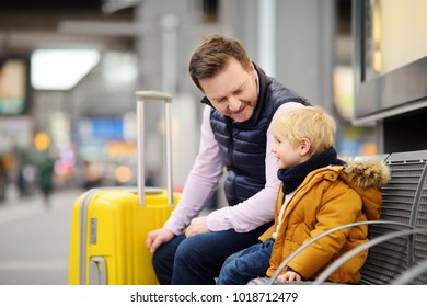 Cute little boy and his father waiting express train on railway station platform or waiting their flight at the airport. Travel, tourism, winter vacation and family concept. Man and his son together.