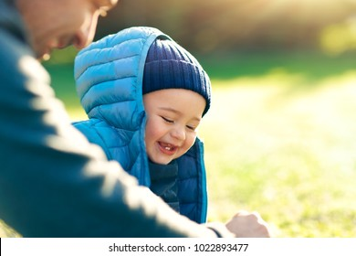 Cute little boy with his father playing outdoors on the fresh green grass field on bright sunny day, happy family with pleasure spending time together, enjoying first spring days