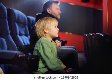 Cute little boy with his father watching cartoon movie in the cinema. Leisure/entertainment for family with kids.