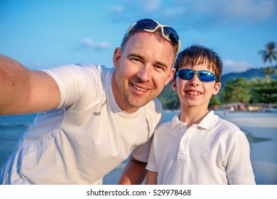 Cute little boy and his father making selfie at tropical beach on exotic island during summer vacation
