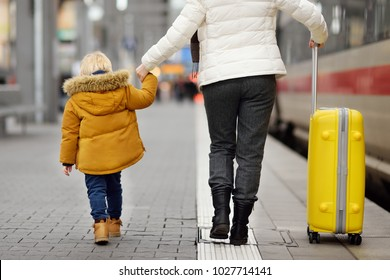 Cute little boy and his grandmother/mother on railway station platform with suitcase. Travel, tourism, winter vacation and family concept. Mature woman and her grandson together.