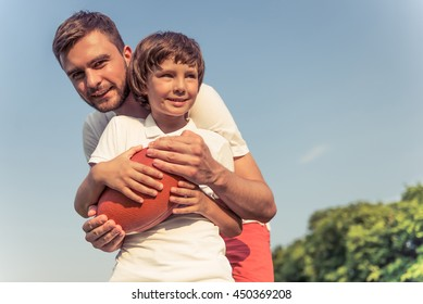 Cute little boy and his handsome young dad are smiling while playing a ball in the park. Father is looking at camera