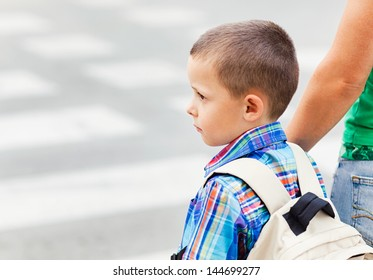 A cute little boy and his mother waiting to cross the street on their way to school.