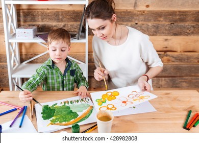 Cute little boy and his mother sitting and paiting bright pictures together