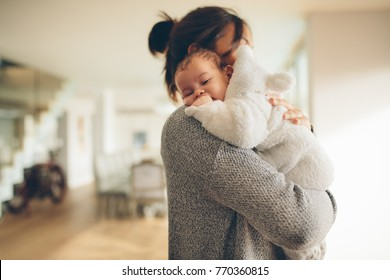 Cute little boy in his mother's arms. Woman at home carrying her newborn son.