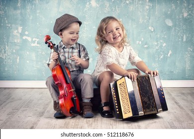 Cute little boy with his old violin is sitting on a suitcase with charming little lady accordion, Retro style.