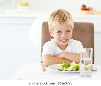 Cute little boy with his salad for lunch sitting at a table in the kitchen