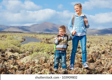 Cute little boy and his sister with backpack have trip in the mountains