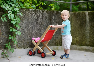 Cute little boy with his toy baby carriage