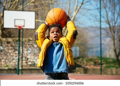Cute little boy holding a basket ball trying make a score