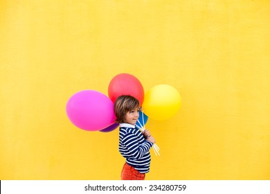 cute little boy holding colors balloons wearing a striped sweater on a yellow wall