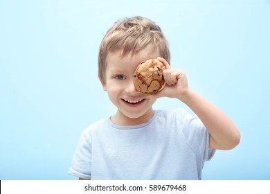 Cute little boy holding cookie on light background