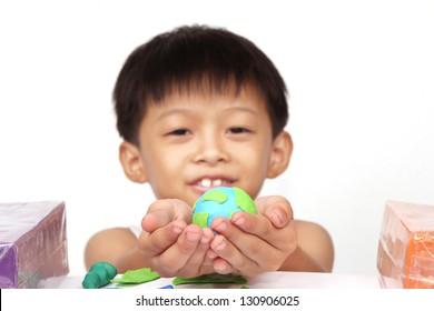 Cute little boy holding hand-made plasticine globe