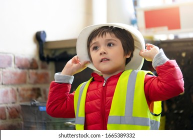 Cute little boy holding helmet and reflective vest, Child pretending a worker constrution wearing safety jacket and helmets costume, Play and learn concept