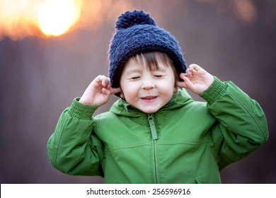 Cute little boy, holding his hands over ears not to hear, making sweet funny face