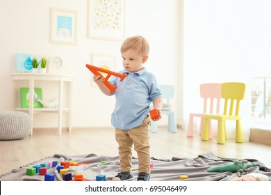Cute little boy holding letter A at home