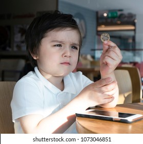 Cute little boy holding one pound coin and looking at money with curious face, Schoolboy sitting in the cofffee shop with mobile phone on table and holding money coin thainking about buy some thing,