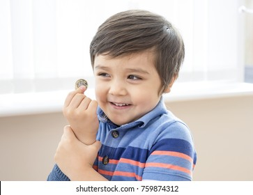 Cute little boy holding one pound coin and looking at  camera with smiling face, Happy boy wearing mismatched clothes with smiling face after got one pound for donation, Children development