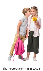 cute little boy holding pink backpack and kissing happy girl holding flowers isolated on white
