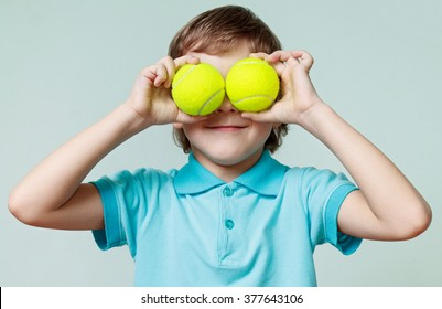Cute little boy holding tennis balls instead of the eyes, blue background