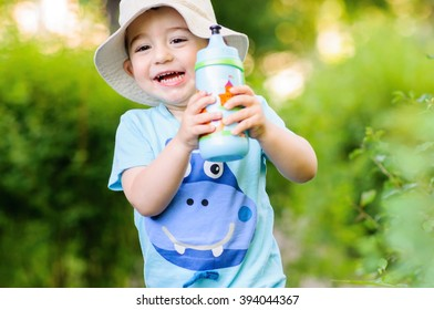 Cute little boy holding a water bottle in park