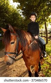 Cute little boy horseback riding in the green at autumn.