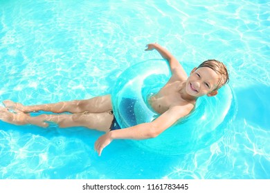 Cute little boy with inflatable ring swimming in pool