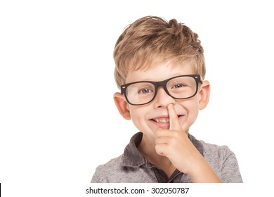 Cute little boy is isolated on white background. Boy wearing glasses, looking at camera, cheerfully smiling and picking his nose