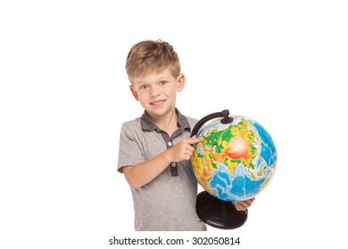 Cute little boy is isolated on white background. Boy looking at camera, smiling and holding globe