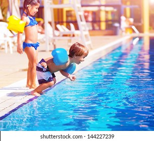 Cute little boy jumping into the pool, brother and sister having fun in poolside, water amusement, luxury beach resort, summer vacation, happy childhood