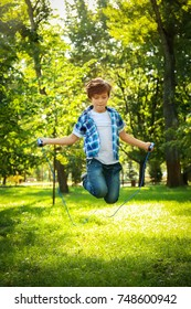 Cute little boy jumping rope in park