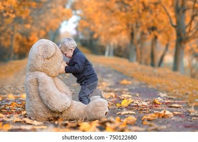 cute Little Boy kissing his Teddy bear in autumn park