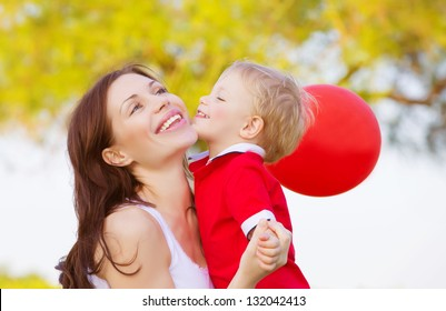 Cute little boy kissing mom, beautiful brunette woman with adorable child having fun outdoor in spring time, small kid with red balloon enjoying nature, happy family