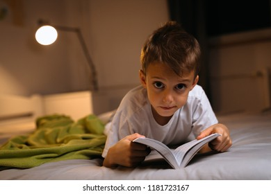 Cute little boy laying in bed and reading book
