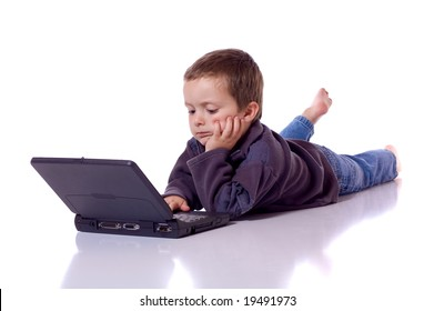Cute little boy laying on his stomach with a laptop